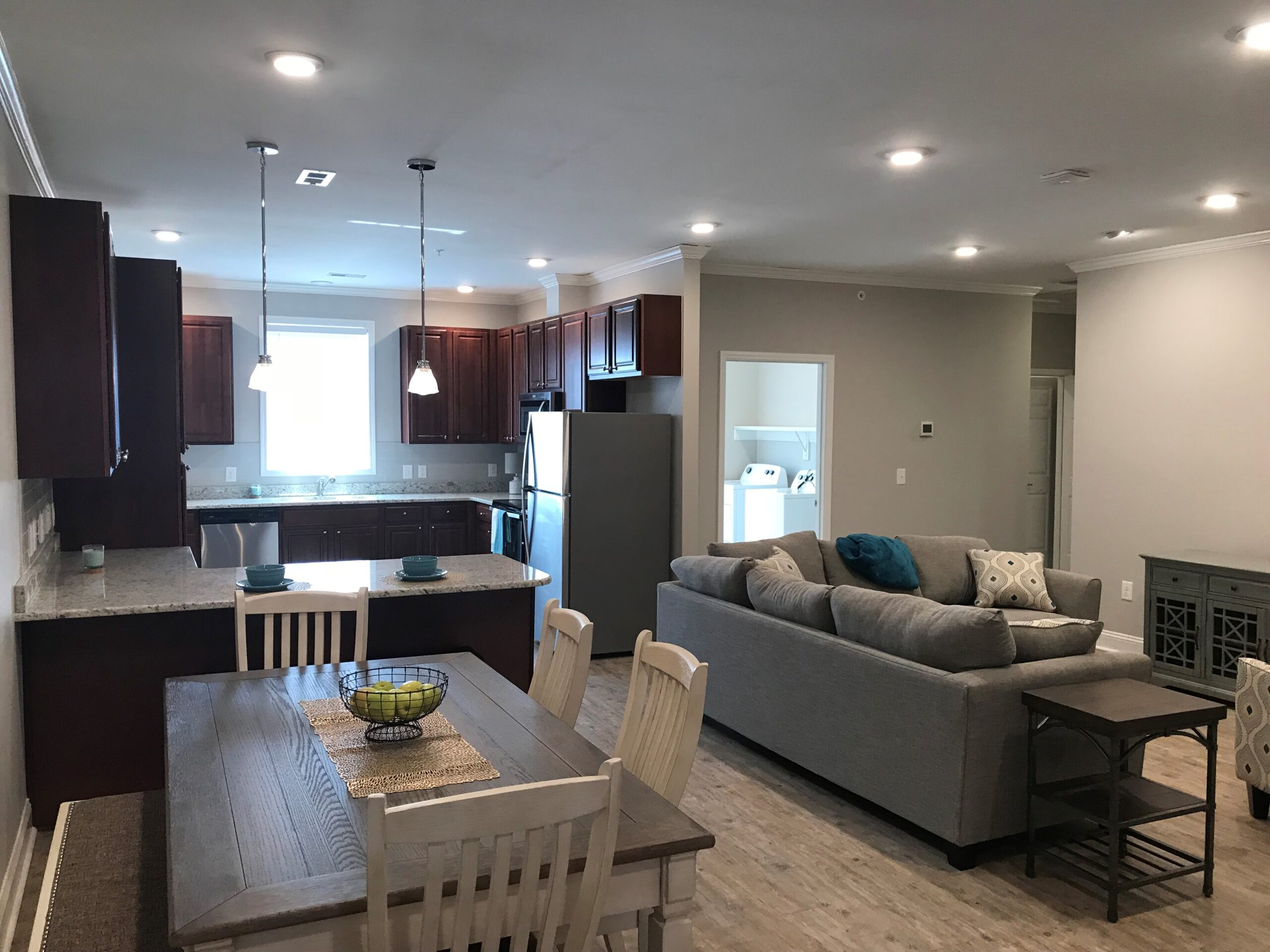 Main room with dining table, couches and kitchen