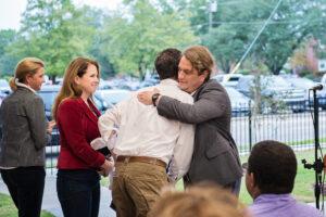 People hugging at outside presentation