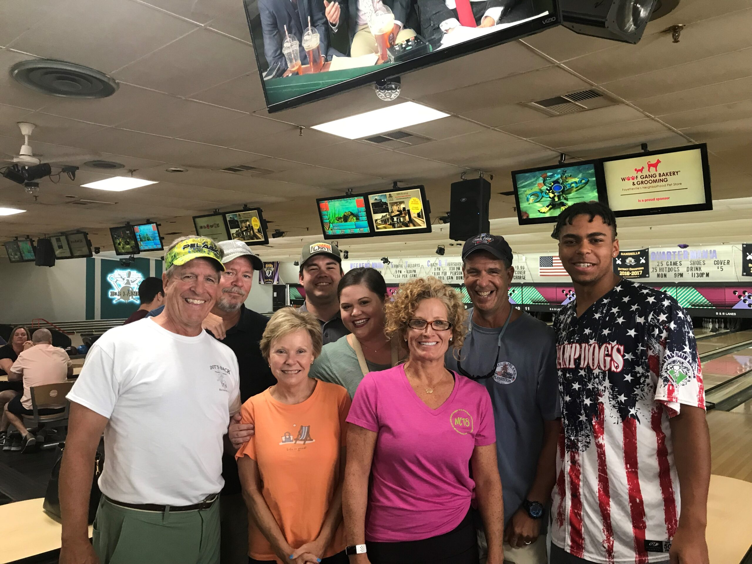 Group of people standing in front of bowling lane