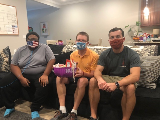 Three people wearing masks sitting on a couch
