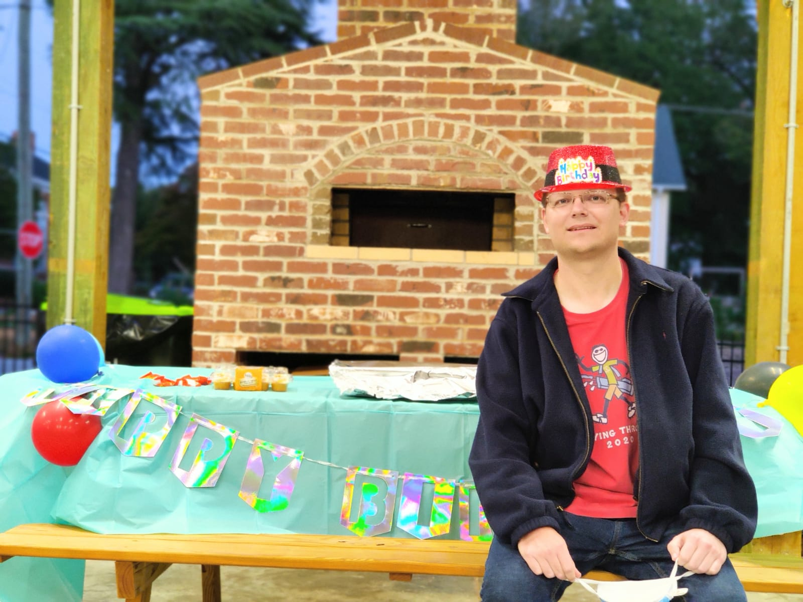 man wearing happy birthday hat sitting on bench outside