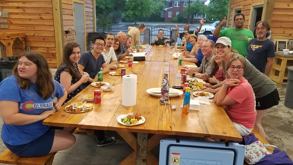 Large group sitting at a picnic table with food outside